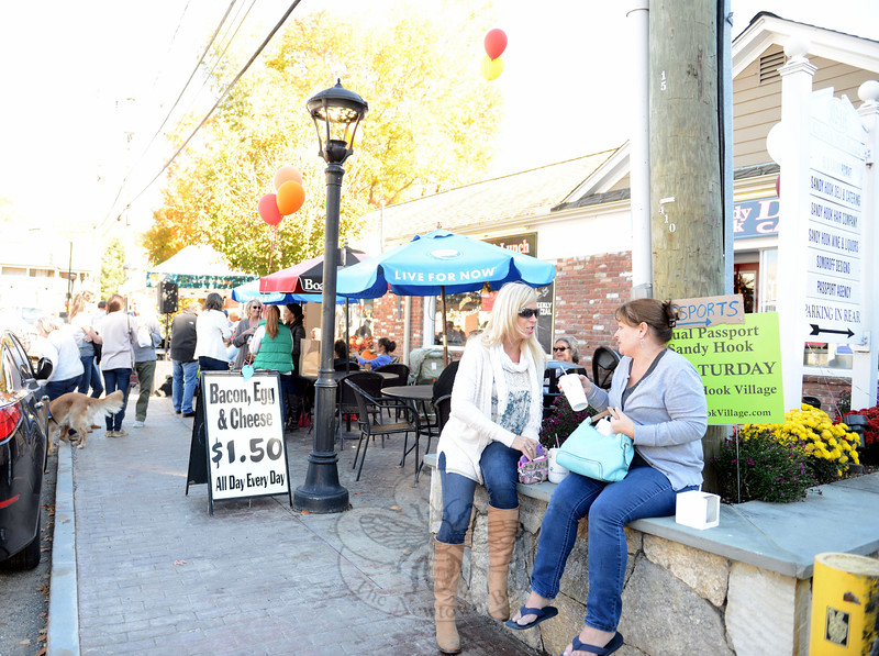 Necole Salvesen, left, and Priscilla Hein perched in a raised stone outside Sandy Hook Deli & Catering late Saturday afternoon. Others found a seat under an umbrella and listened to a band that had set up under an awning further down the sidewalk.(Bobowick photo)