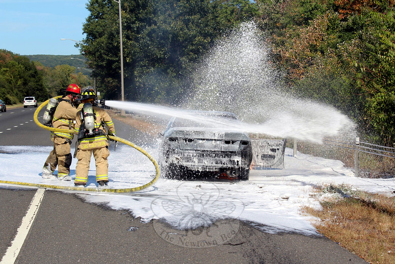 Sandy Hook Volunteer Fire & Rescue firefighters responded to a car fire on I-84 East that was reported shortly after 2 pm Sunday, September 27. Upon arriving, firefighters — including Lieutenant John Jeltema, left, and EMS Captain Karin Halstead — encountered a 1999 Toyota Camry that was fully engulfed in flames, but the male driver had been able to get out and away from the vehicle without injury. State troopers also responded to the incident, which caused long traffic delays. (Hicks photo)