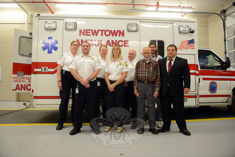 Volunteers and supporters from Newtown Volunteer Ambulance Service, from left, back row, Megan Posey, James Wolff, NVAC Chief Mike Collins, and Anthony Raiani; front row, Roger Connor, Jennifer Newsom, and Dr Bob Grossman, join volunteer EMT Chris Capozza who is organizing a November 14 CT CHIP child safety registration event at the new ambulance headquarters at Fairfield Hills in conjunction with Hiram Lodge No. 18 in Sandy Hook. (Bobowick photo)