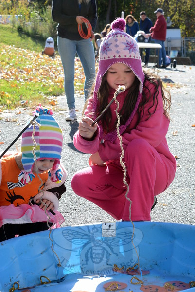 Cousins Rachel Venezia, 2, and Morgan Capone, 9, go fishing for pumpkins and bats. (Hutchison photo)