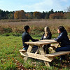 From left, Monica Roberto and Harmony Verna of The Animal Center, and Jenny Hubbard sit at a picnic table placed on property deeded to the Catherine Violet Hubbard Foundation, last month, for the creation of an animal sanctuary. The Animal Center in Newtown has joined with the foundation to work toward that goal. (Crevier photo)