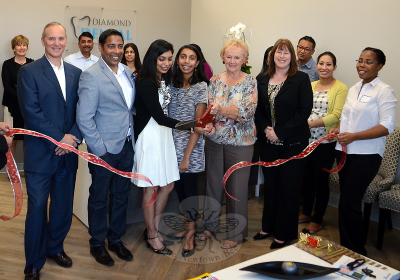 Diamond Dental Opens At Sand HillFirst Selectman Pat Llodra helps the owners and staff at Diamond Dental in Sand Hill Plaza celebrate the office's grand opening October 21 with a ribbon cutting. In attendance are, from left, Sand Hill Plaza developer Paul Scalzo, Krishna Mohan, daughter Monisha, Ratna Vedullapalli, DDS, Mrs Llodra, and Economic Development Commission Chair Jean Leonard.   (Voket photo)