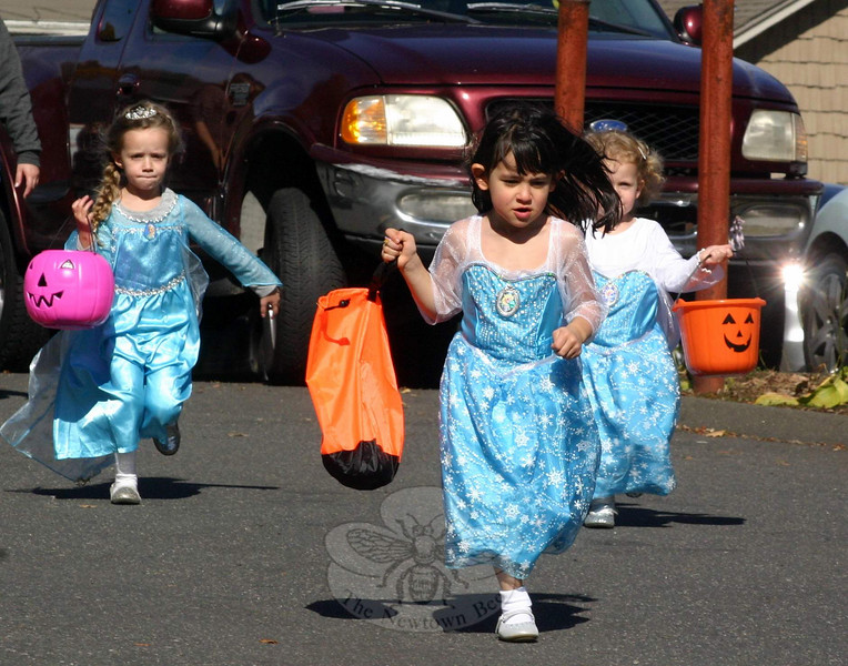 Three young girls dressed as Elsa, one of the princesses in Disney's Frozen, run toward one of their candy destinations last weekend during the Fourth Annual Sandy Hook Halloween Walk. Young girls in the light blue gowns seemed to be everywhere for a few hours on October 25, as children dressed up to give their costumes a trial run (literally, in this case) in a daytime event in Sandy Hook Center. Nearly two dozen local businesses welcomed visitors through their doors. Sandy Hook Volunteer Fire & Rescue also had a truck and table set up in the parking lot of 100-102 Church Hill Road for Saturday's special event, which was hosted by Sandy Hook Organization for Prosperity. (Hicks photo)