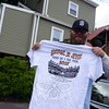Terrence Ford displays T-shirts for this year's Shuck and Jive Mountain Bike and Music Festival, which will take place on Friday through Sunday, October 9-11, in Sandy Hook. Three days of bands and mountain biking will fill the McLaughlin Vineyard fields and trails off Albert's Hill Road. (Bobowick photo)