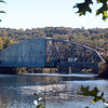 As seen from the town park off Bridge End Farm Lane, rehabilitation work is progressing on Silver Bridge, which spans the Lake Zoar section of the Housatonic River, linking Glen Road in Sandy Hook to River Road in Southbury. A tarpaulin covers a section of the bridge where painting is underway. The span is carrying one-way alternating traffic to allow the project to proceed. When completed, the bridge which has been brown, will be painted a silvery color. The 308-foot-long bridge was built in 1936. For decades it had been a silvery paint color, which led to generations of local residents referring to the span as Silver Bridge (which is, officially, Bridge 00507 in state records). A past improvement project resulted in the bridge being painted its current brown. McNamee Construction Corp of Lincolndale, N.Y., is doing the $4.47 million project for the state Department of Transportation. (Gorosko photo)