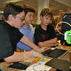 From left, Rodney Colon, John Boccuzzi III, and Eli Kirby look over the Thingiverse online design sharing site. The selected design was then created in the library's newest 3D printer, which can be seen on the table near Eli. The library's original, smaller 3D printer is in the foreground. (Crevier photo)