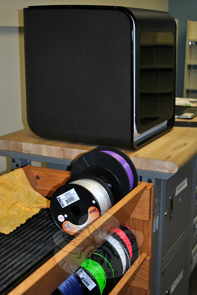 Spools of colored plastic thread are stored near the new Afinia 800 3D printer that arrived at the library the end of August. The new printer can make larger projects, has a more even heating/cooling capability, and can make objects using multiple colors. (Crevier photo)