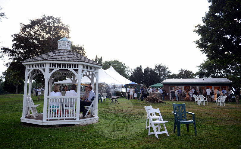 An approaching storm around sunset Saturday did not discourage all guests at the NFA's 90th anniversary celebration. Many found cover in a nearby gazebo, or the gallery, right, while others simply tolerated a light drizzle before heavy rain fell. (Bobowick photo)