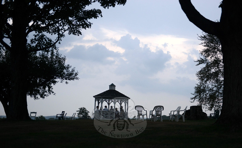 A handful of guests retreat to a hilltop gazebo, hoping for a little relief from a storm rolling in Saturday, September 6, over the Holcombe Hill Wildlife Preserve — Newtown's highest point. Only empty chairs remain where other guests promptly left the evening's Sunset Wine Tasting celebration marking Newtown Forest Association's 90th anniversary. (Bobowick photo)