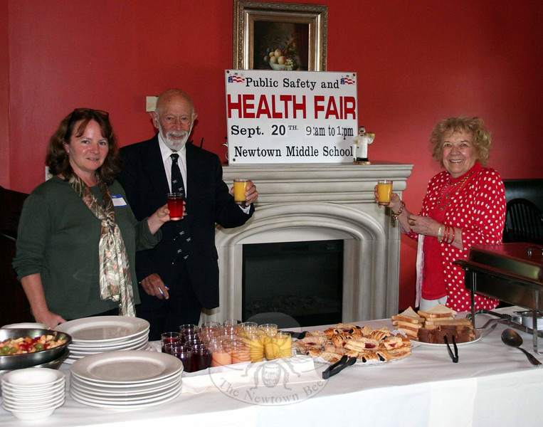 Health Fair Planning Committee members Donna Culbert, left, and Mae Schmidle were joined by Newtown Volunteer Ambulance Association representative Dr Robert Grossman on September 9 raised glasses of fruit juice to toast the progressing plans for this year's fair. Dozens of health and public safety agencies and organizations have signed up for the September 20 event. (Hicks photo)