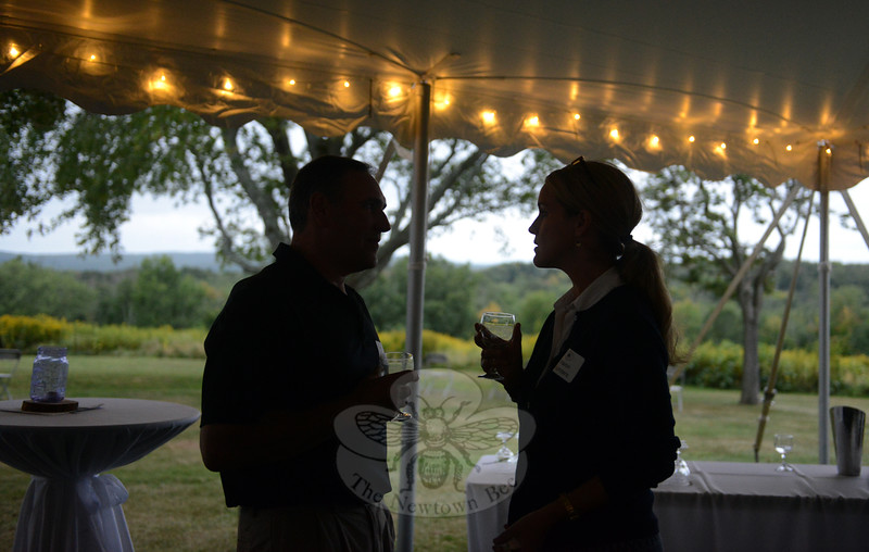Sharing a drink and quiet conversation Saturday were Mark Krasnickas and Sharon Saunders. They sampled wine as dusk fell at Holcombe Hill Preserve during Newtown Forest Association's Sunset Wine Tasting event. (Bobowick photo)