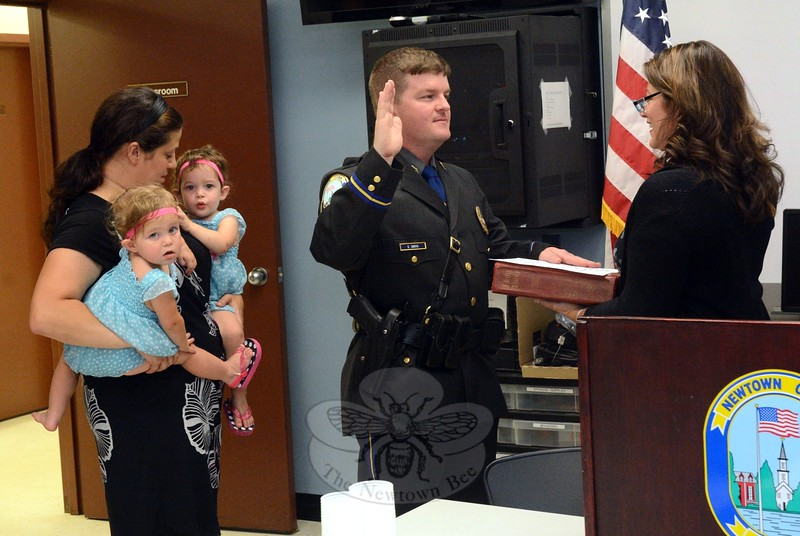 Scott Smith took his oath of office as a sergeant from Town Clerk Debbie Aurelia Halstead in September 8 ceremonies at the police station. Looking on are Sergeant Smith's wife Sara, who is holding their twin daughters Natalie and Nora. (Gorosko photo)