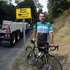 As a flatbed tractor-trailer truck hauls a load of cast-concrete items northward on Botsford Hill Road, Steven Tramposch, a member of Sound Cyclists Bicycle Club, is shown standing next to a traffic sign explaining that state law requires motorists to stay at least three feet away from bicyclists in motion. The town has posted such traffic signs along town roads that are popular bicycling routes. (Gorosko photo)