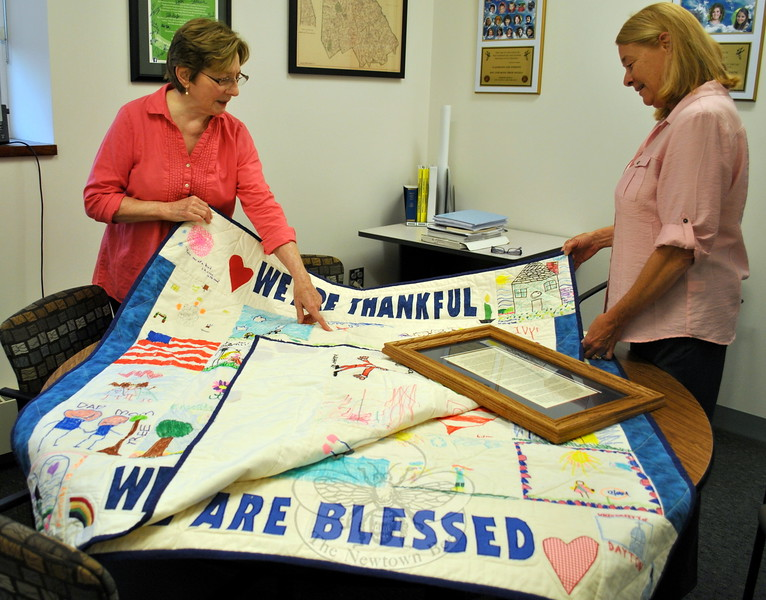Jan Brookes, left, points out a detail on one of two comfort quilts she has made to Newtown Human Resources Administrator Carole Ross. The quilts were made in response to the loss of a special quilt received in Newtown after 12/14, and will be on display at Newtown Municipal Center for the next month. (Crevier photo)
