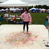 "Dark skies and a threat of rain did nothing to damper or diminish the enthusiasm of volunteers, performers, artists and visitors to the second annual Newtown Arts Festival. The month-long celebration's ""main event"" was staged over September 13 and 14, drawing folks to Fairfield Hills, including artist Dave Brooker who enlisted visitors Mjellma Abazi (center) and Elise Dickman creating a huge piece of public art. (Voket photo)"