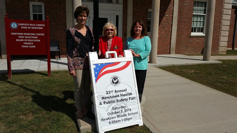Three of the four Co-Chairs of the 22nd Annual Health & Safety Fair are pictured by one of the signs popping up around town calling all community members to this year's showcase and informational event, set for October 3, from 9 am to 1 pm, at Newtown Middle School. From left, Dr Della Schmid, Mae Schmidle, and Health District Director Donna Culbert, along with Judy Blanchard, the school district's Recovery Project Director and Prevention Council Co-Chair are promising loads of free screenings, giveaways, raffles, family safety tips, and introductions to dozens of health and safety professionals. (Voket photo)