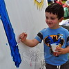 Ian Sachs helped paint a sign at the Ben's Lighthouse tent during the first day of the Newtown Arts Festival signature outdoor event on Saturday, September 20.