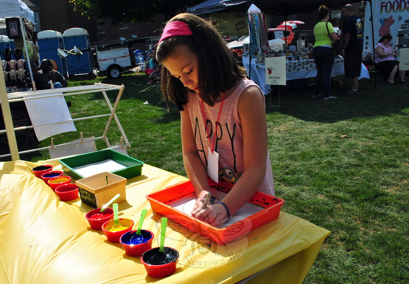 The 2015 Newtown Arts Festival was held on Saturday, September 20, and Sunday, September 21. On the first day of the festival, Maddie Kistner made art with paint and marbles at the Fraser Woods Montessori School tent. (Hallabeck photo)