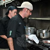 Chef Justin Kern controls the flames of a tequila chili sauce, while sous chef C.J. Donahue looks on. Chef Kern, executive chef, and Mr Donahue, both of Newtown, oversee the kitchen at Meeting House Pub in Bethel, and will compete in the September 18 Chefs Challenge in Shelton. The public event is a benefit for Optimus Foundation. (Crevier photo)
