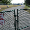 A padlocked gate positioned at a rear driveway that provides emergency-vehicle access to the 37-acre Newtown High School campus from Oakview Road. Police Commission members, acting as the local traffic authority, this week rejected a request from high school officials to allow that driveway to be used by some school staff members for morning access to the property.  (Gorosko photo)