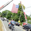 Among the hundreds of riders passing through several Fairfield County towns including Newtown on Sunday was one man with a fist raised as he passed under the raised flag on South Main Street. (Bobowick photo)