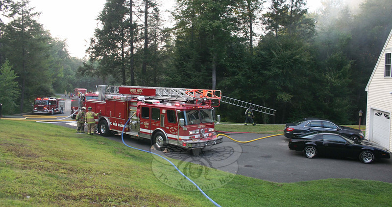 Firefighters pumped water from the edge of Alpine Circle (background) to the top of the driveway, about 300 feet, to get water into the hoses of those working to douse Tuesday's fire.  (Hicks photo)