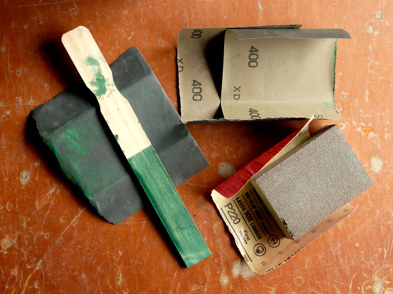Tools of the sanding trade: surface prepping with successive use coarse to fine 150, 220, and wet 400 grit sandpapers.