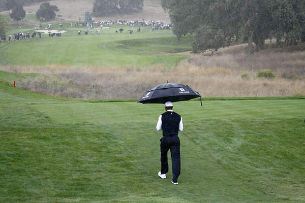 Tiger Woods heads up the fourth hole as the rain falls at the Fry's.Com Open PGA golf tournament Thursday, Oct. 6, 2011 in San Martin, Calif. (AP Photo/Dino Vournas)