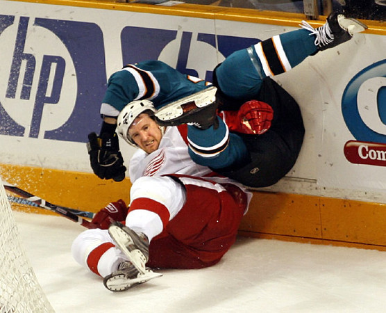 The San Jose Sharks' Ryan Clowe, top, knocks the Detroit Red Wings' Niklas Kronwall into the boards in the first period of an NHL hockey game, Saturday, Jan. 17, 2009 in San Jose, Calif.  AP Photo/Dino Vournas