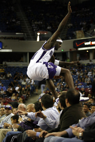 Sacramento Kings Justin Williams leaps over the front row of seats in the fourth quarter of an NBA preseason basketball game against the Phoenix Suns, Thursday, Oct. 11, 2007 in Sacramento, Calif.  (AP Photo/Dino Vournas)