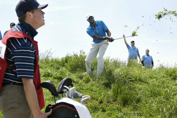 With his caddie Andy Miller, left, watching, Jerry Rice hits out of the rough at the tenth hole at the Nationwide Tour's Fresh Express Classic at TPC Stonebrae, Thursday, April 15, 2010 in Hayward, Calif.  AP Photo/Dino Vournas