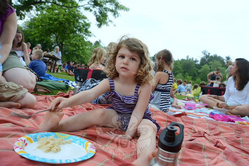 Ivy Masotta has a quick picnic lunch before the first performance of a children's concert series begins at Dickinson Park.  (Bobowick photo)