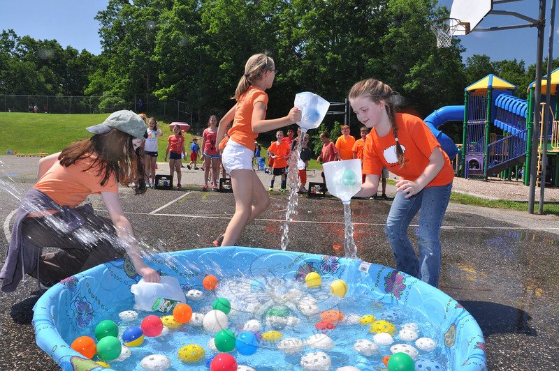 "Students scooped up plastic balls amid the spray of a hose during at the ""apple barrel fill"" station during Middle Gate School's annual Field Day on Monday, June 17.   (Dietter photo)"