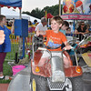Sam Irving gives a thumbs up from the seat of a race car ride on the opening night of the St Rose Parish Carnival, Tuesday, June 25. The annual event will continue on the parish grounds until Saturday, June 29, running nightly from 6 to 10:30 pm. The carnival features rides and games by Stewart Amusement, as well as a kiddie tent with face painting and crafts, and nightly entertainment. There are plenty of food offerings, and the St Rose Home and School Association will host a Friday Night Bingo on June 28. Admission for Bingo is $17 per person, which includes all regular and some special games. Carnival food will be available for Bingo players, and can be purchased through student waiters. Proceeds from this year's carnival will be used to support parish needs.   (Dietter photo)
