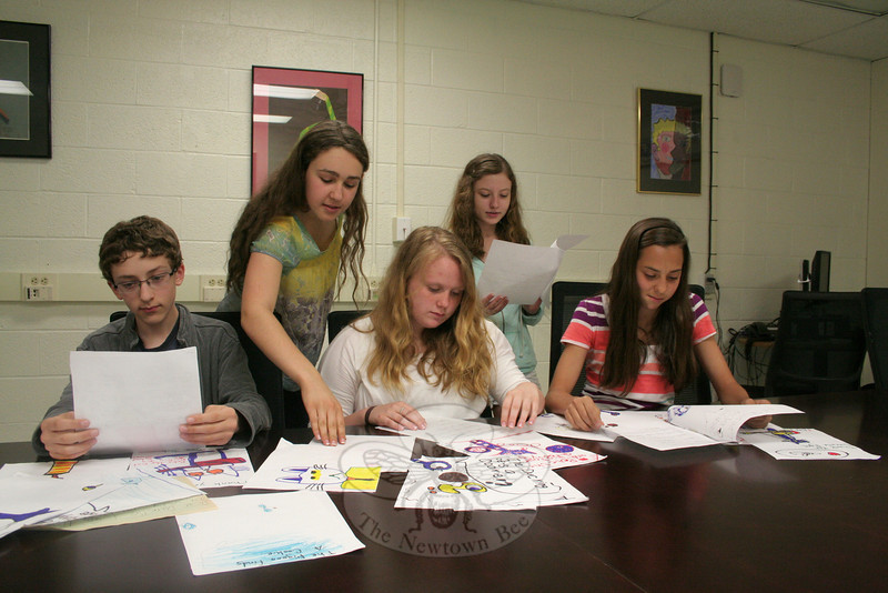 Newtown Middle School 8 Purple Cluster students learned the value of paying kindness forward this past spring. From left are Sam Zakur, Kathryn Blanco, Emily McCoy, Kate Luongo, and Lauren Russo, looking at some of the thank-you notes they received from a first grade class in Detroit after the eighth graders decided to send books to them. That first gesture of kindness led to a second one by NMS students before the end of the school year.  (Hicks photo)