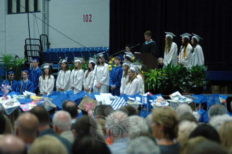 "Newtown High School teacher Lee Keylock, at the podium, gives the commencement address during the graduation ceremony for NHS's Class of 2013, with assistance from students and NHS teacher Jane Matson.  (Hallabeck photo)<br /> <br />  PLEASE NOTE: Additional photos from this event, which were presented online in a slide-show, can be viewed here:<br />  <a href=""http://photos.newtownbee.com/Journalism/Special-Events/Newtown-High-School-Class-of/30241881_rDjLT8#!i=2603084990&k=22SXVwZ"">http://photos.newtownbee.com/Journalism/Special-Events/Newtown-High-School-Class-of/30241881_rDjLT8#!i=2603084990&k=22SXVwZ</a>"