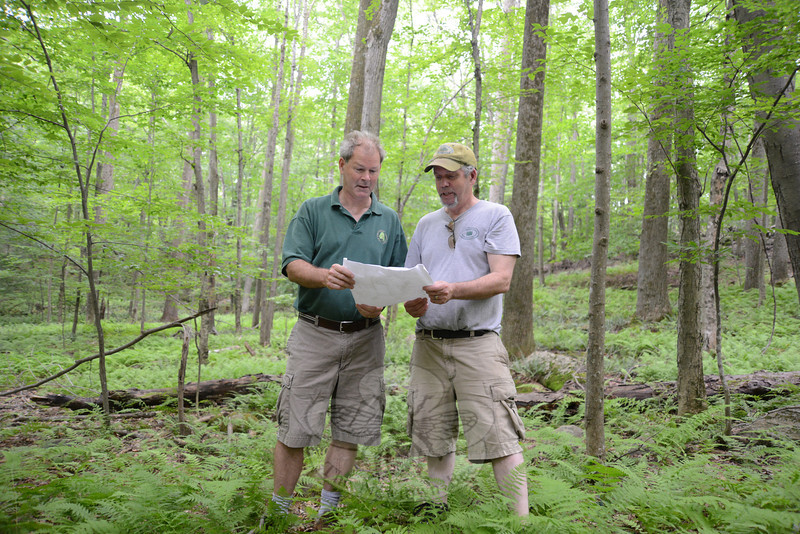 Newtown Forest Association (NFA) Vice President Bart Smith, left, and President Bob Eckenrode look at area maps for the NFA's recently purchased property at 196 Hattertown Road.  (Bobowick photo)