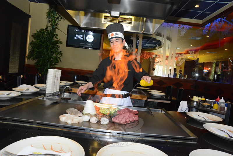Chef Benny Chen adds a dash of oil and sparks tall flames from the griddle centered among dining seats where he prepares steak, a tower of sliced onion, fresh vegetables, shrimp, scallops, and sea bass.  (Bobowick photo)
