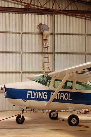 A volunteer helps fix the hangar door.
