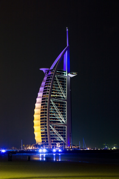 The Burj Al Arab at night.  The building is lit by coloured lights, which change every few minutes.