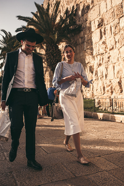 A modren jewish couple walks along the old city of Jerusalem.