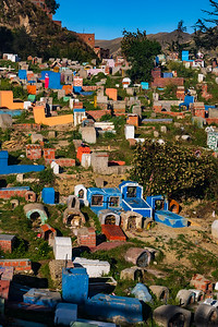 Colorful graves dot the steep hillside
