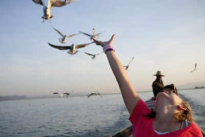 Ana feeds the seagulls from our boat on Inle Lake, Burma (Myanmar).