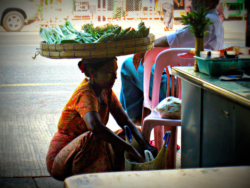A woman sells vegetables from a tray on her head throughout the streets in Yangon, Myanmar (Burma)