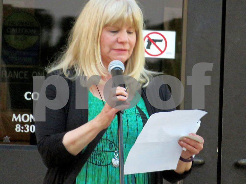 Mary Ellen Schaid, executive director for Safe Passage in DeKalb County, reads remarks during a vigil honoring Lidia Juarez, who was shot and killed by her estranged husband last month.