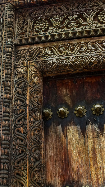 """In Stone Town, Zanzibar, the merchants """"advertised"""" with the carvings on their doors. Even though slavery and the ivory trade were made illegal, the chain and tusk carvings incorporated into the door indicate that one could purchase both here."""