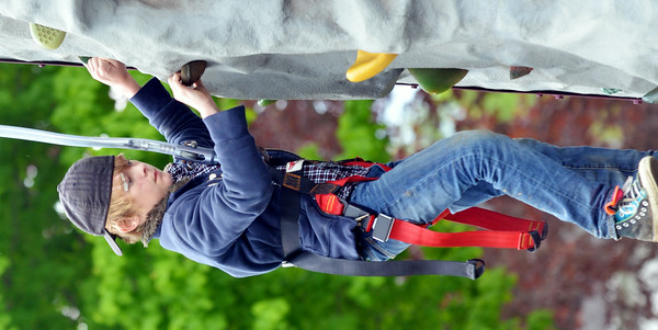 WARREN DILLAWAY / Star Beacon MATTHEW SONGER, 12, of Sheffield Township, works a rock climbing wall on Saturday during the 40th Kingsville Lawn Sale.