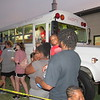 CATHY SPAULDING/Muskogee Phoenix<br /> People line up for snow cones served from Shorty, a ministry bus, at Timothy Baptist Church's Independence Day celebration. Shorty also goes to city parks, downtown and the Dr. Martin Luther King Jr. Community Center.