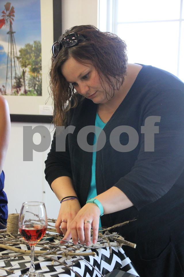 Kati Swanson holds part of the decoration on her craft project in place while the hot glue dries. She was taking part in the Soldiers Creek Winery's Un'Wine'd craft night event held there on Thursday, July 16, 2015 .