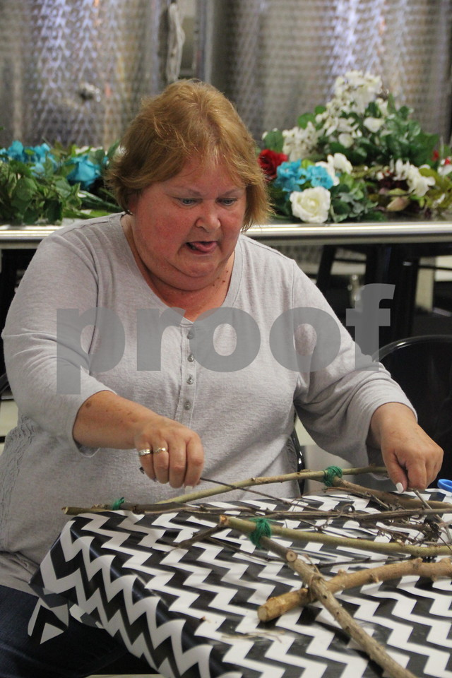Cathy Campbell concentrates on her craft project she is making at craft night on Thursday, July 16, 2015, held at Soldiers Creek Winery.